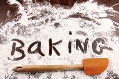 Exprima o cozimento escrito na farinha branca na tabela de madeira Imagem de Stock