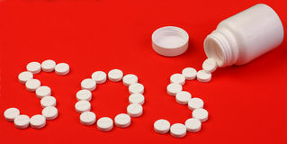 Palavra SOS feita dos comprimidos Imagens de Stock