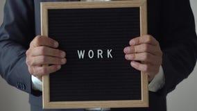 Exprima o trabalho das letras na placa do texto nas mãos anônimas do homem de negócios vídeos de arquivo