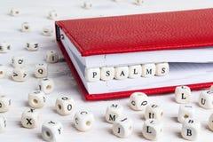 Exprima os salmos escritos em blocos de madeira no caderno vermelho no wo branco fotos de stock royalty free
