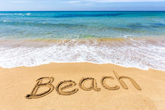 Exprima a praia escrita na areia no mar grego Foto de Stock Royalty Free