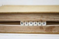 Exprima a recompensa escrita em blocos de madeira no livro Imagem de Stock Royalty Free