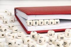 Exprima a reforma escrita em blocos de madeira no caderno vermelho no wo branco imagem de stock