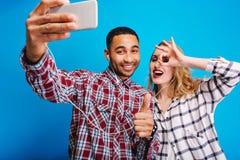 Exprimant des émotions positives brightful de la jeune femme blonde joyeuse ayant l'amusement avec le type beau sur le fond bleu photo stock