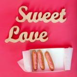 Exprime l'amour doux, lettres en bois sur le papier rose avec la boîte ouverte de petits gâteaux frais Fond de jour du ` s de Val Photos libres de droits