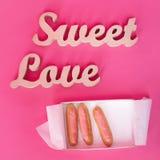 Exprime l'amour doux, lettres en bois sur le papier rose avec la boîte ouverte de petits gâteaux frais Fond de jour du ` s de Val Photo libre de droits