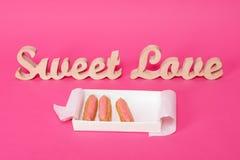 Exprime l'amour doux, lettres en bois sur le papier rose avec la boîte ouverte de petits gâteaux frais Fond de jour du ` s de Val Images stock