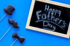 Exprime le jour heureux du ` s de père écrit sur le tableau noir Biscuits de lien noir, de moustache et de chapeau Vue supérieure Photo libre de droits
