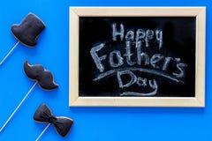 Exprime le jour heureux du ` s de père écrit sur le tableau noir Biscuits de lien noir, de moustache et de chapeau Vue supérieure Image stock