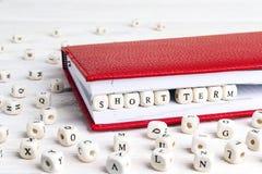 Exprimez à court terme écrit dans les blocs en bois dans le carnet rouge sur le wh image stock