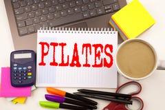 Exprimez écrire Pilates dans le bureau avec l'ordinateur portable, marqueur, stylo, papeterie, café Concept d'affaires pour la sé photos stock