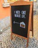 """Exprimez-""""moi ont besoin de gâteau parce que la vie """"sur annoncer le conseil noir sur la rue image libre de droits"""