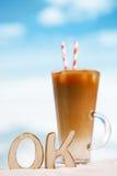 exprimez CORRECT avec le latte glacé de café sur un océan de plage image libre de droits