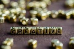 Exprimez CRÉATIF fait à partir de petites lettres d'or sur le backgr brun image libre de droits