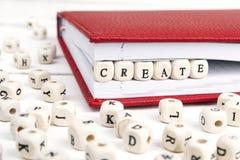 Exprimez Create écrite dans les blocs en bois dans le carnet sur en bois blanc photo libre de droits