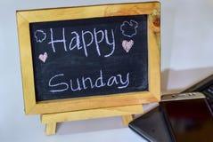 Exprimez dimanche heureux écrit sur un tableau sur lui et le smartphone, ordinateur portable photos libres de droits
