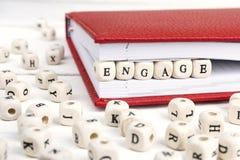 Exprimez Engage écrit dans les blocs en bois dans le carnet sur en bois blanc image libre de droits