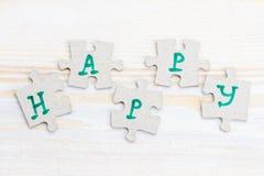 Exprimez heureux fait de quatre morceaux de puzzle denteux sur en bois léger photographie stock libre de droits