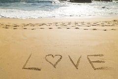 Exprimez l'amour écrit dans le sable d'une belle plage Photo libre de droits
