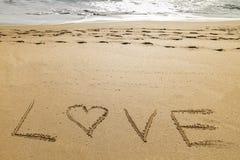 Exprimez l'amour écrit dans le sable d'une belle plage Image libre de droits
