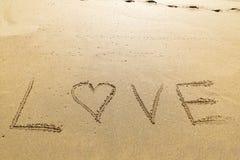 Exprimez l'amour écrit dans le sable d'une belle plage Photos stock