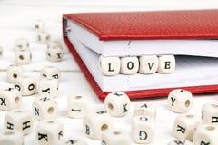 Exprimez l'amour écrit dans les blocs en bois dans le carnet sur en bois blanc Photos stock