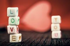 Exprimez l'amour écrit dans les blocs en céramique avec hors du coeur de foyer à l'arrière-plan Photo stock