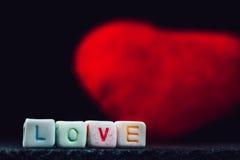 Exprimez l'amour écrit dans les blocs en céramique avec hors du coeur de foyer à l'arrière-plan Photographie stock