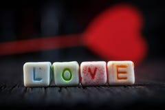Exprimez l'amour écrit dans les blocs en céramique avec hors du coeur de foyer à l'arrière-plan Photographie stock libre de droits