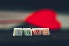 Exprimez l'amour écrit dans les blocs en céramique avec hors du coeur de foyer Photo stock