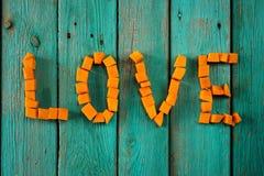 Exprimez l'amour écrit par les cubes lumineux doux en potiron sur le CCB de turquoise Photographie stock libre de droits