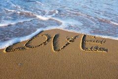 Exprimez l'AMOUR écrit sur le sable à la plage Photographie stock libre de droits