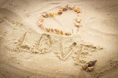 Exprimez l'amour écrit sur le sable à la plage, coeur des coquilles Photos libres de droits