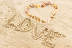 Exprimez l'amour écrit sur le sable à la plage, coeur des coquilles Photographie stock libre de droits