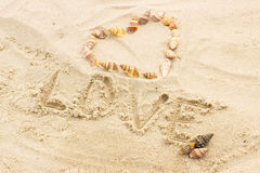 Exprimez l'amour écrit sur le sable à la plage, coeur des coquilles Photographie stock