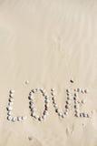 Exprimez l'amour écrit sur le sable avec des coquilles de mer au coucher du soleil sur la plage Images stock