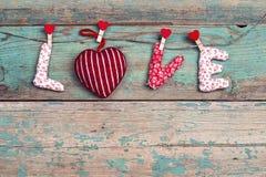 Exprimez l'amour avec le coeur accrochant sur la pince à linge sur le vieux bois de turquoise Photo libre de droits