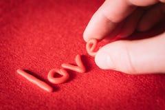 Exprimez l'amour avec les lettres rouges sur un fond rouge Photo stock