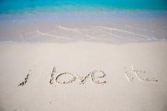Exprimez l'amour d'I il manuscrit sur la plage sablonneuse avec le ressac mou sur le fond Photos stock