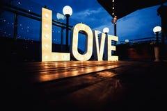 Exprimez l'amour de grand, lettres avec les ampoules rougeoyantes sur un b foncé Photographie stock