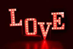 Exprimez l'amour de grandes, rouges lettres avec les ampoules rougeoyantes sur un fond foncé Photographie stock libre de droits