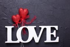 Exprimez l'amour et deux coeurs rouges sur le fond noir Photos libres de droits
