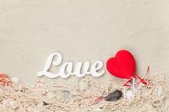 Exprimez l'amour et la forme de coeur de jouet sur le filet et les coquilles Images stock