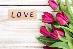 Exprimez l'AMOUR et le bouquet des tulipes sur le fond en bois Photographie stock