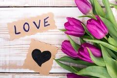 Exprimez l'AMOUR et le bouquet des tulipes sur le fond en bois Image stock