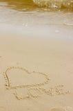 Exprimez l'amour et le coeur écrits sur le sable à la plage par la mer Photo libre de droits