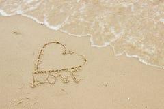 Exprimez l'amour et le coeur écrits sur le sable à la plage par la mer Photos stock