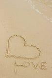 Exprimez l'amour et le coeur écrits sur le sable à la plage par la mer Images libres de droits