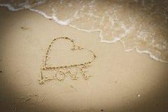 Exprimez l'amour et le coeur écrits sur le sable à la plage par la mer Image libre de droits