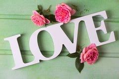 Exprimez l'amour et les fleurs de roses sur le fond en bois vert Photos stock